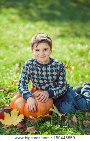 Boy Resting on a Pumpkin on green grass and autumn leaves
