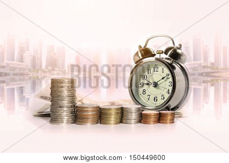 Group of a row of stack money coins and analog clock on the blurred cityscape background concept for business finances and saving money.