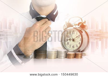 Double exposure of businessman in white shirt with a row of stack money coins and analog clock on the blurred cityscape background concept for business finances and saving money.
