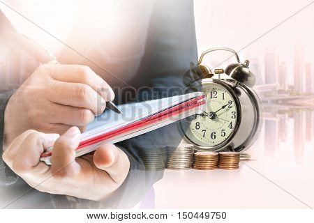 Double exposure of businesswoman take notes on the book with a row of stack money coins and analog clock on the blurred cityscape background concept for business finances and saving money.