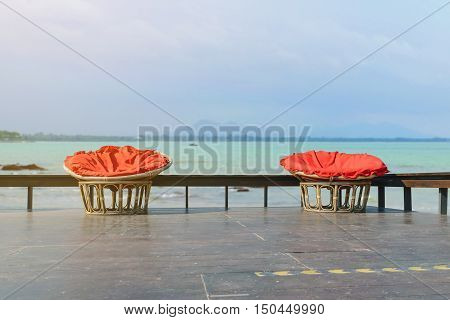 Chairs made of rattan and upholstery fabrics in red on wooden terrace with the backdrop of the ocean.