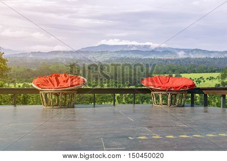 Chairs made of rattan and upholstery fabrics in red on wooden terrace with the backdrop of the forest.