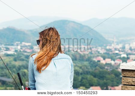 Woman looks into the distance on the mountain town. Woman enjoying the mountain landscape of the town