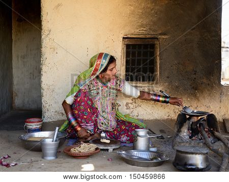 BHUJ INDIA - JANUARY 13: The ethnic woman in the village on the desert in the Gujarat state is preparing the cake to pies chapati in the kitchen by one's house Bhuj in January 13 2015