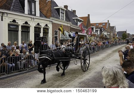 WORKUM, THE NETHERLANDS - SEPTEMBER 28, 2016: An male gig driver, dressed in period Frisian costume, driving a Frisian carriage horse through a street in the city of Workum, the Netherlands.