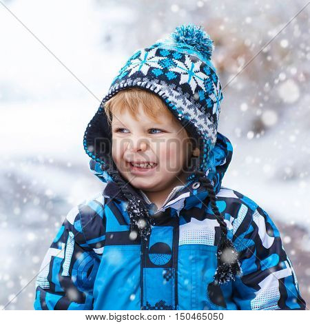 Winter portrait of funny kid boy in colorful clothes, outdoors during snowfall. Active outoors leisure with children in winter on cold snowy days. Happy toddler child having fun with snow in forest