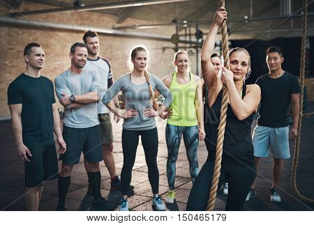 Group of adults watching woman use climbing rope in fitness exercise circuit training regimen