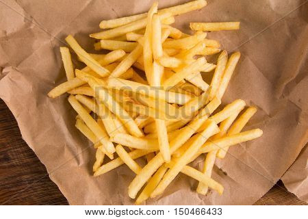 Fried potatoes on brown paper at wooden table. Fastfood