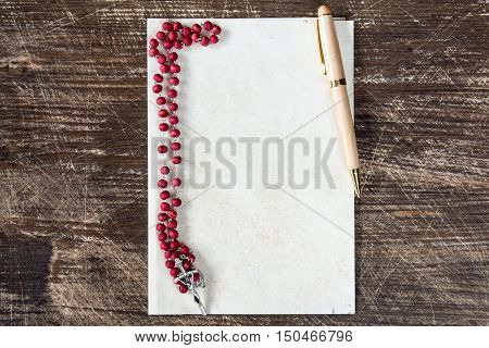Catholic rosary and pen on blank paper sheet with copy-space