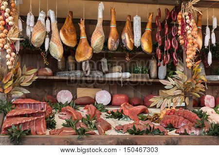 Meat Assortment And Sausages In Butcher Shop On Wooden Board