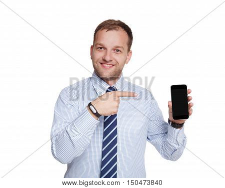 Make a call. Young happy succesful businessman with mobile phone or smartphone points finger on it, isolated on white. Portrait of smiling man in trendy blue shirt and tie.
