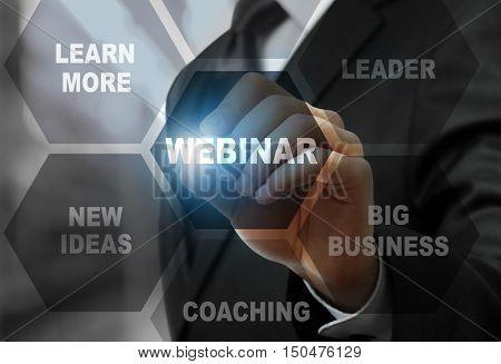 Businessman pushing WEBINAR button on virtual screen. Business coaching and modern technology concept.