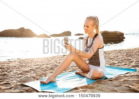 Attractive happy young woman doing yoga and using cell phone sitting on mat outdoors on beach