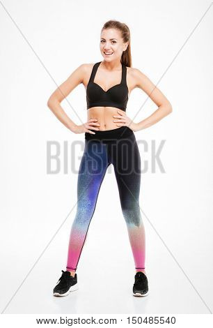 Smiling attractive young fitness woman in sportwear standing and posing over white background