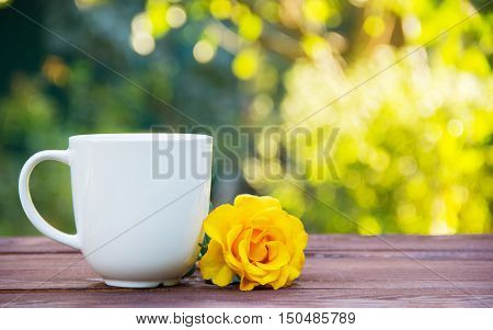 White cup of tea on a wooden table. Teatime in the open air. Copy space poster