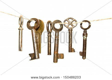 Many keys hanging on a rope on over white