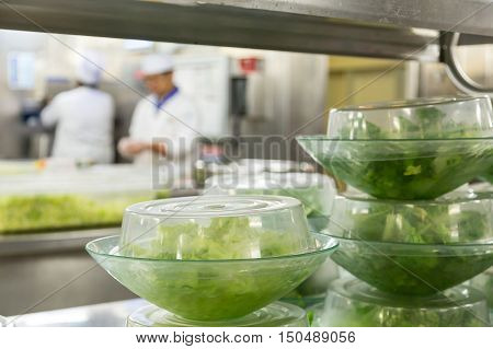 Salads Prepped with Chefs in the Background