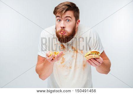 Excited hungry bearded man greedily eating hamburgers isolated on white background