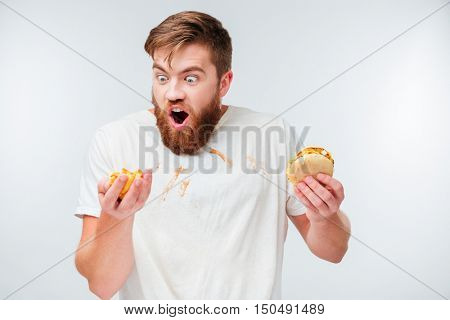 Hungry bearded man in filthy shirt eating hamburgers isolated on white background