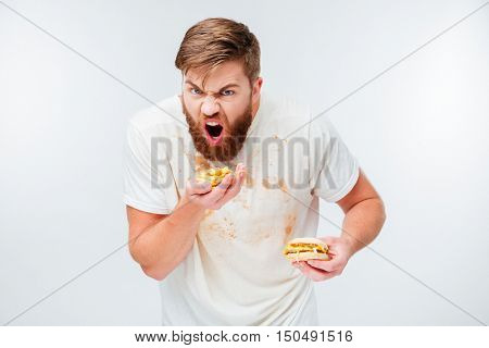 Excited hungry bearded man greedily eating hamburgers isolated on white background