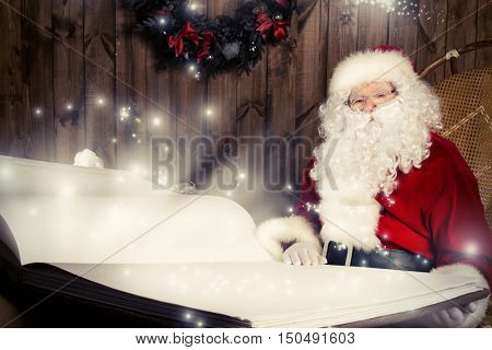 Santa Claus reading magic book in his wooden house. The magic of Christmas.