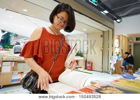 SHENZHEN, CHINA - SEPTEMBER 09, 2016: chinese woman read book at a book store in Shenzhen. Shenzhen is a major city in Guangdong Province, China.