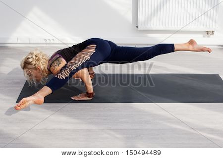 Yogi woman doing handstand on the mat at the gym