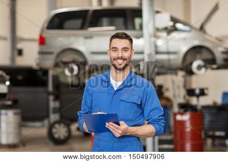 car service, repair, maintenance and people concept - happy smiling auto mechanic man or smith with clipboard at workshop