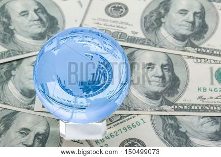 Blue glass earth sphere with north america in front on a layer of hundred dollar bills global business concept
