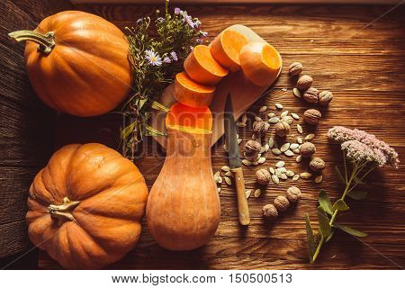 On old wooden table lie pumpkins walnuts pumpkin seeds autumn flowers. Pumpkins on a wooden table. Fresh pumpkin crop. Nova harvest vegetables. Autumn vegetables. Pumpkin.