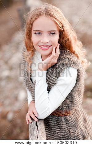 Smiling blonde kid girl 13-14 year old wearing fur vest and white sweater outdoors. Autumn season. Childhood.