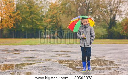 Sad Child Walking In Rubber Wellingtons On Wet Footpath.