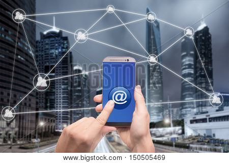 Hand holding smartphone and click on button with at sign linked with people icons. Email marketing newsletter and bulk mail concepts.