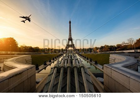 Airplane flying over Eiffel Tower in morning Paris France. Eiffel Tower is international landmark in Paris France