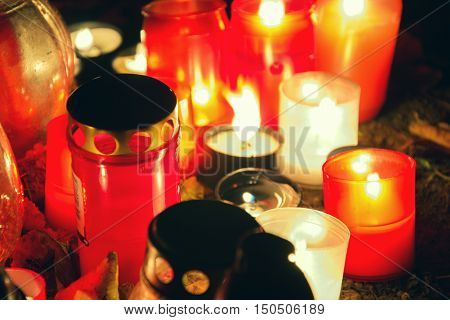 Votive candles lantern burning on the graves in Slovak cemetery at night time. All Saints' Day. Solemnity of All Saints. All Hallows eve. 1st November. Feast of All Saints. Hallowmas. All Souls' Day poster