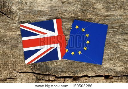 Brexit concept half blue european union EU flag on wooden background and half Great Britain flag. British vote to leave EU