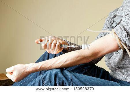 Internet addiction creative concept: junkie gives himself a vine using syringe