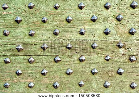 green old boards with metal rusty studs