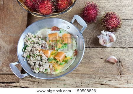 Indochina pan-fried egg with pork and sausage toppings on wood table. Rambutan fruit.
