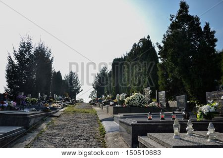 TOPOLCANY SLOVAKIA - 30.10.2015: Graves tombstones and crucifixes on traditional cemetery. Votive candles lantern and flowers on tomb stones in graveyard. All Saints' Day. All Souls' Day