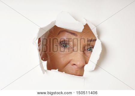 close-up watchful older woman looking through hole poster