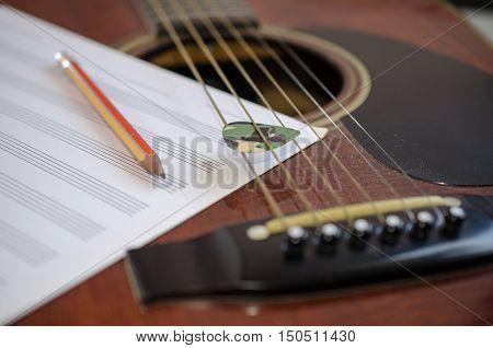 Composer tool. Guitar guitar pick an eraser a pencil.