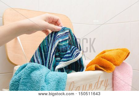 Woman put dirty towels into laundry basket