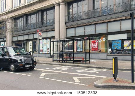 LONDON UK - March 26: Whiteleys shopping center bus stop with people sitting on the bench while waiting in London UK - March 26 2016; Public bus stop in London urban street with black cab on the side.