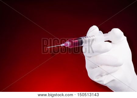 Hand pushing bloody syringe on red background