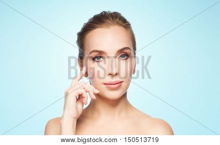 beauty, people and plastic surgery concept - beautiful young woman showing her cheekbone over blue background