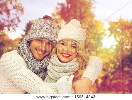 season, people, love and fashion concept - happy family couple in warm clothes over autumn background