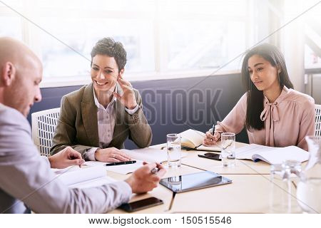 Business meeting between three executive employees, two female and one male, taking place in a birght conference table early in the morning to prepare for the week ahead.