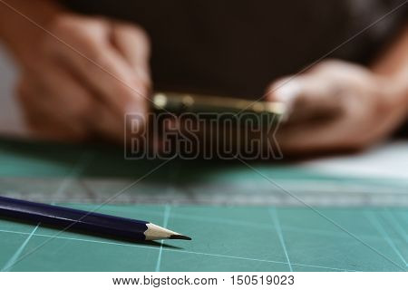 closeup of a young caucasian man using a smartphone at his office desk, where there is a sharpened pencil and a ruler
