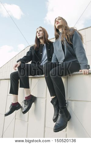 two young fashion woman sit on parapet low angle